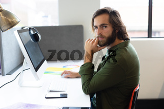 Portrait of caucasian man sitting at desk in creative office