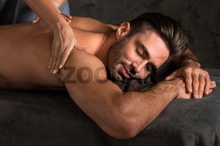 Man getting back massage at spa