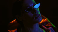 Portrait shot of a beautiful girl wearing down jacket and sunglasses in neon color lights . Pretty girl in neon light on black background. Night club, Party. Night portrait of girl and neon lights