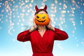 woman in halloween costume of devil with pumpkin