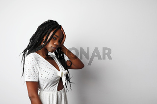Young black woman with sad, pensive, reflective look, against white wall background with copy space for your text .