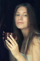 Portrait of young blonde woman with coffee cup in hands behind the window glass with raindrops.
