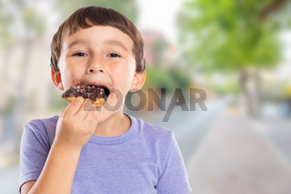 Portrait of a young boy child eating donut town copyspace copy space unhealthy sweet sweets