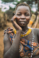 TOPOSA TRIBE, SOUTH SUDAN - MARCH 12, 2020: Young woman with traditional scars of Toposa Tribe touching face and looking at camera on blurred background of village in South Sudan, Africa