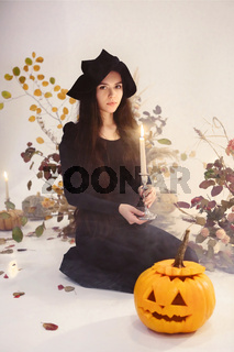 Woman in witch costume with pumpkin