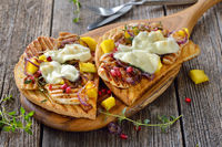 Large toast with chicken and mango and pomegranate seeds