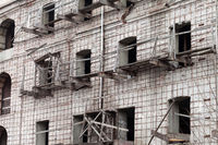 Brick wall of old destroyed house without windows with wooden broken scaffold