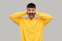 man in yellow sweatshirt closing ears by hands