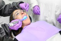 Young woman receiving ultraviolet light procedure at dentist office