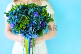 A wedding bouquet with hydrangea in blue and green colors outdoors