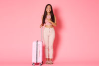 Travelling, holidays and vacation concept. Full-length of dreamy attractive asian girl explore country while being abroad, pointing finger left and smiling curious, standing with suitcase, pink wall