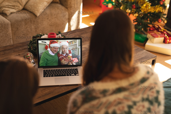 Rear view of woman and son having a videocall with senior couple in santa hats opening gift box on l