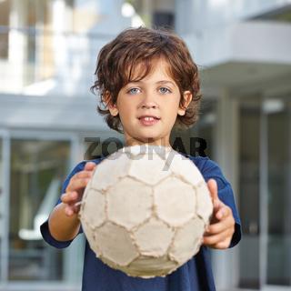 Kind hält Fußball nach vorne