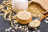Flour oat in bowl with oatmeal on dark wooden board