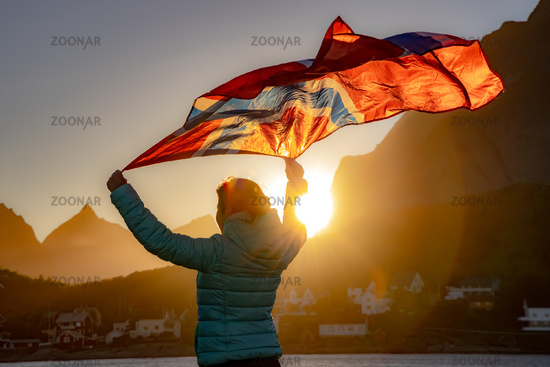 Woman waving the flag of Norway at sunset