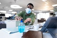 Businessman wearing face mask sanitizing his hands at modern office