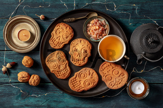 Halloween ginger cookies in the shape of skulls, homemade Dia de los muertos biscuits, shot from above with tea and candles