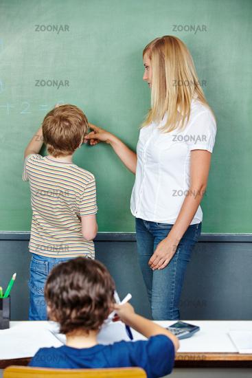 Schüler löst Aufgabe an Tafel