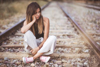 Portrait Of a Young Sad woman, Sitting pensive Outdoors On The Railway track.