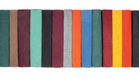 Stack of old hardcover books on bookshelf. Close-up view of multicolored vintage hardback books. Iso