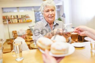 Seniorin im Seniorencafe holt sich am Tresen Pfannkuchen und eine Tasse Kaffee