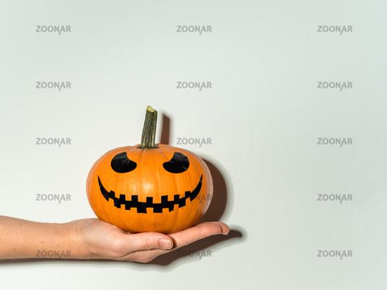 Halloween pumpkin in hand on white wall background
