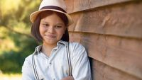 A lovely girl in a hat and shirt with suspenders stands leaning against a wooden house or barn looks at the camera