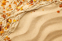 Ambers And Fishing Net Composition On Sand