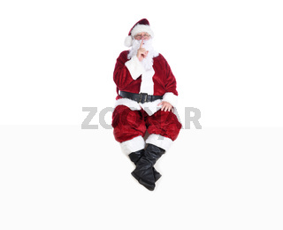 Senior man in traditional Santa Claus Suit sitting on a white wall with a finger to his lips making a Shh Gesture.