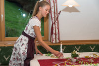 attractive waitress in dirndl dress covers hotel table - table decoration