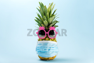COVID Travel concept. Pineapple in sunglasses and medical mask on a blue background. Pineapple in pink sunglasses and face mask - New normal travel