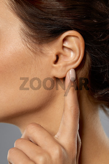 close up of young woman pointing finger to her ear