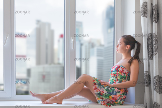 Woman sitting on windowsill during global coronavirus outbreak. stay at home and self isolation