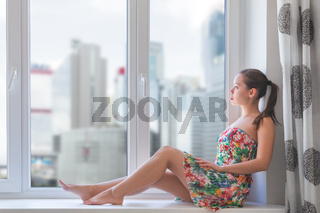 Young woman sitting on windowsill during global coronavirus outbreak. stay at home and self isolation concept