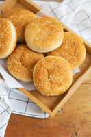 Freshly baked hamburger buns lie on a wooden tray on the table with a white napkin. Yellow flavored pastries with white sesame seeds.