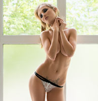 Slim blonde posing topless on window sill