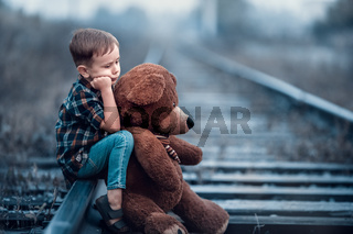 A little boy with a big teddy bear sits on the rails of the railway. Loneliness and sadness of a child.