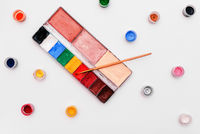 Palette with paints and brush on a white background. Colored small jars of paint. Set of artist for make-up and drawing. Training in drawing and art.