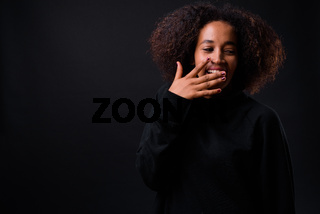 Young beautiful African woman with Afro hair against black background
