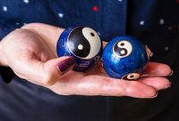 A woman holds two blue qigong balls  with yin and yang symbols in her hand