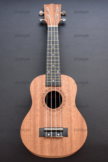 A brown soprano ukulele on black background