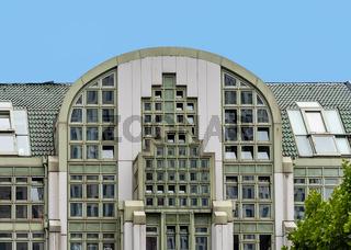 Modern commercial building with green metalic facade against blue sky in Kurfurstendamm in Berlin