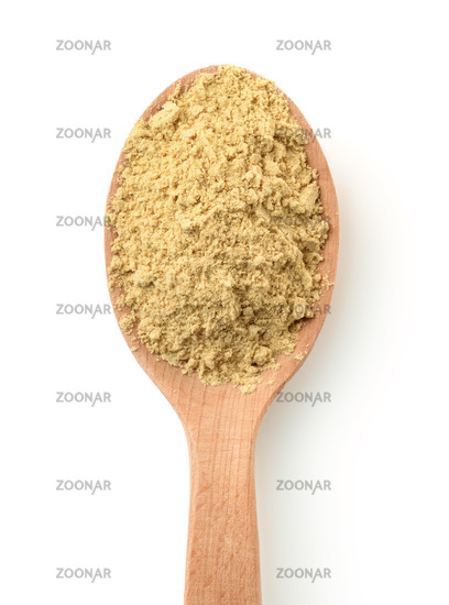 Top view of mustard powder in wooden spoon