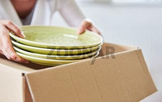 Frau packt Teller in einen Umzugskarton