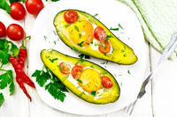 Scrambled eggs with tomatoes in avocado on wooden board top