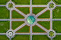 Symmetrial aerial view at a green park with a temple in its center, straight top down from above, popular architecture photo.