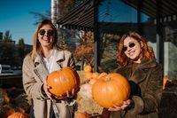 Girls holds pumpkins in hands. Outdoor photo.