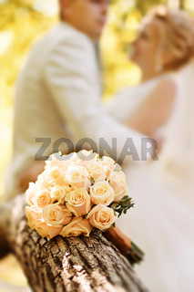 bridal bouquet of roses against the background of the bride and groom