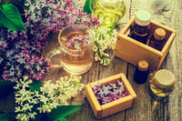 Essential oil and a cup of tea made from lilac flowers
