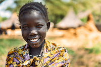 BOYA TRIBE, SOUTH SUDAN - MARCH 10, 2020: Girl in traditional colorful outfit and accessory smiling at camera against blurred settlement in South Sudan in Africa